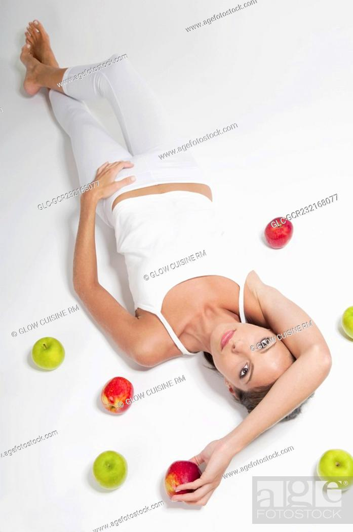 Stock Photo: High angle view of a woman lying with red and green apples.