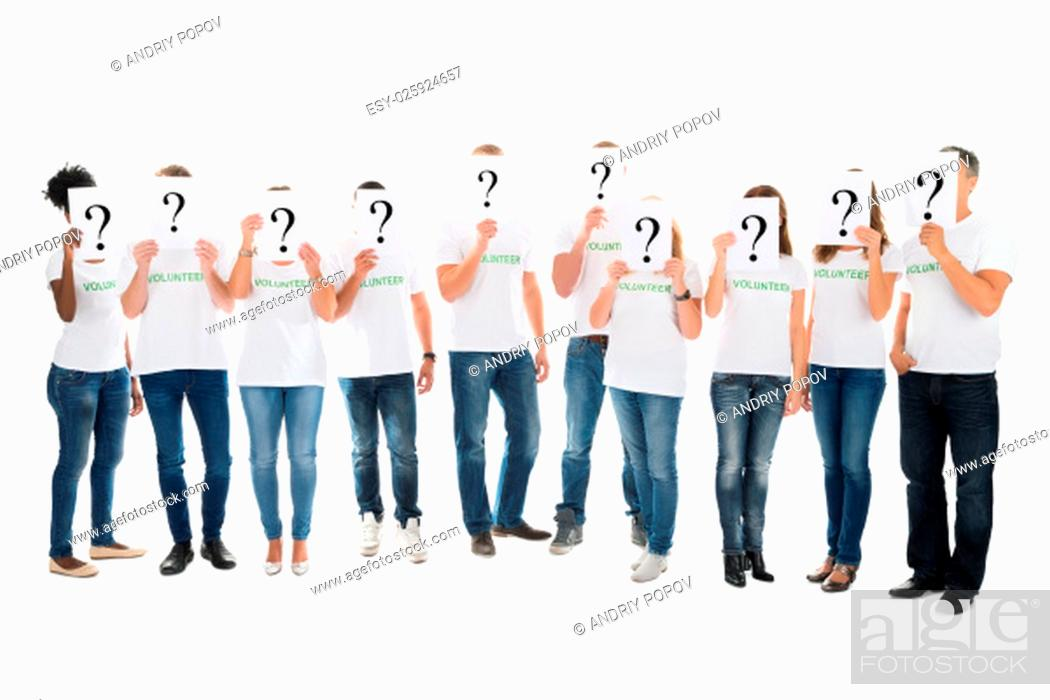 Stock Photo: Full length of volunteers covering faces with question mark signs against white background.