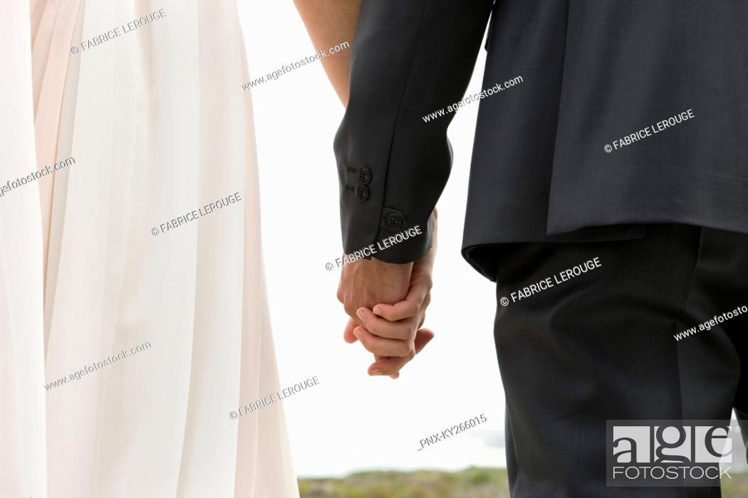 Stock Photo: Rear view of a couple holding hands.