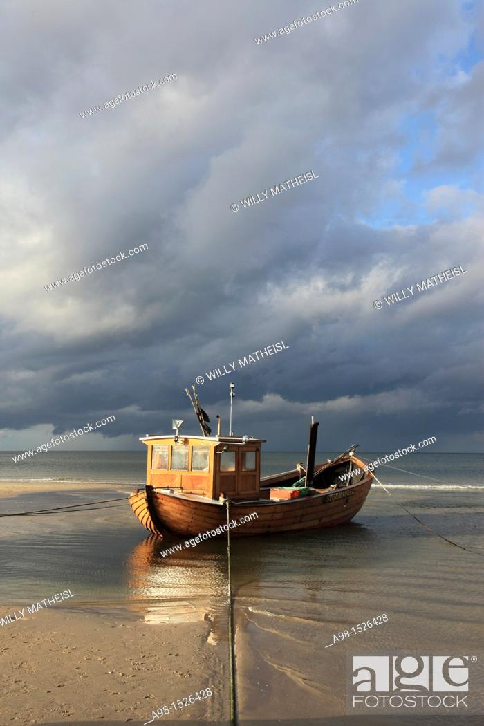 Imagen: traditional wooden Fishing boat on the beach in the seaside resort of Ahlbeck in sunlight before thundershower, Usedom, Mecklenburg-Vorpommern, Germany, Europe.