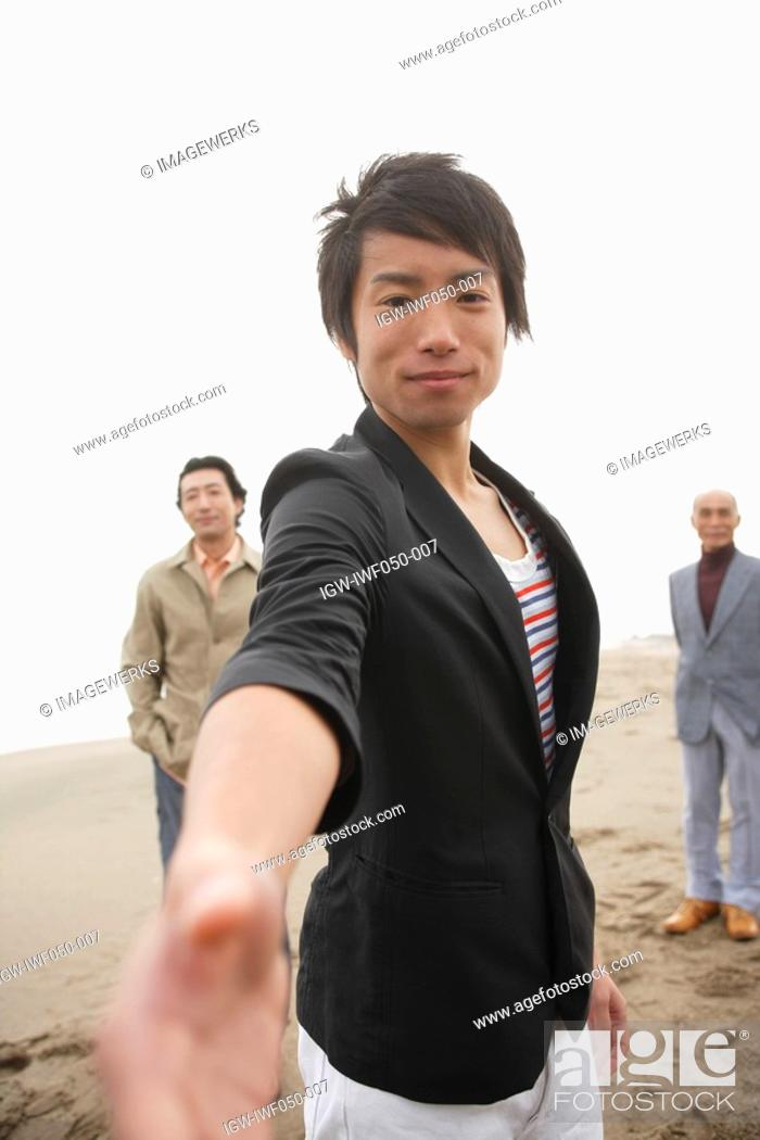 Stock Photo: Young man smiling while father and grandfather standing in background.
