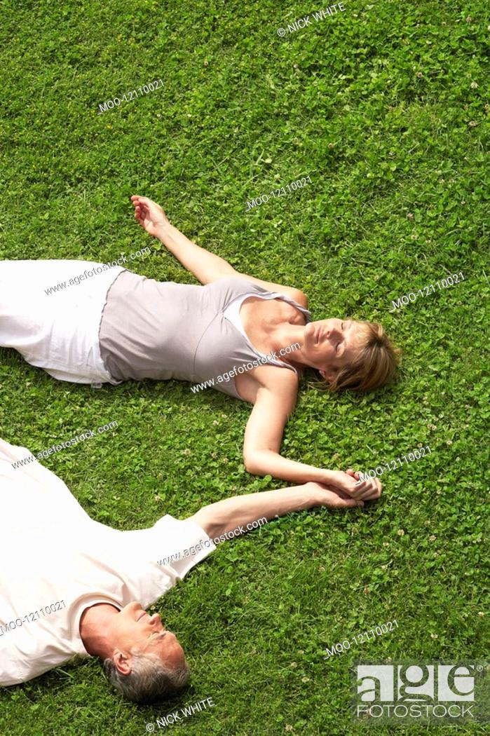Stock Photo: Middle-aged couple together sleeping on grass high angle view.
