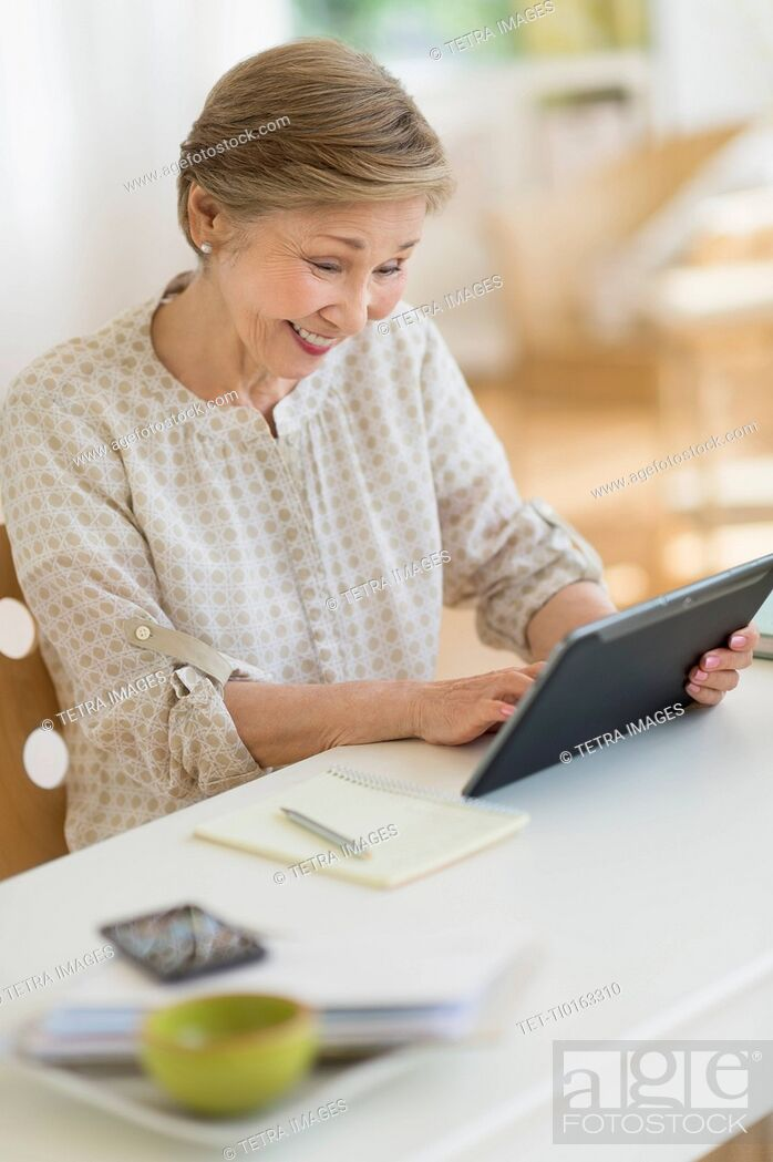 Stock Photo: Senior woman using tablet pc at home.