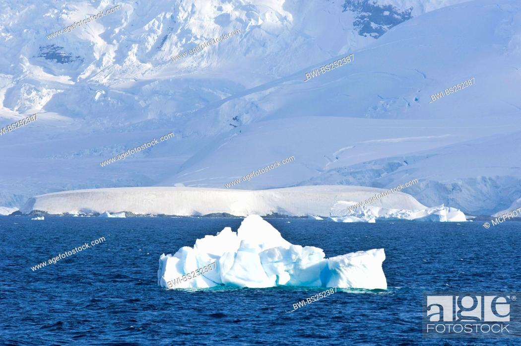 Imagen: mountain massive looming at the edge of the Gerlache Strait with iceberg in the foreground, Antarctica.