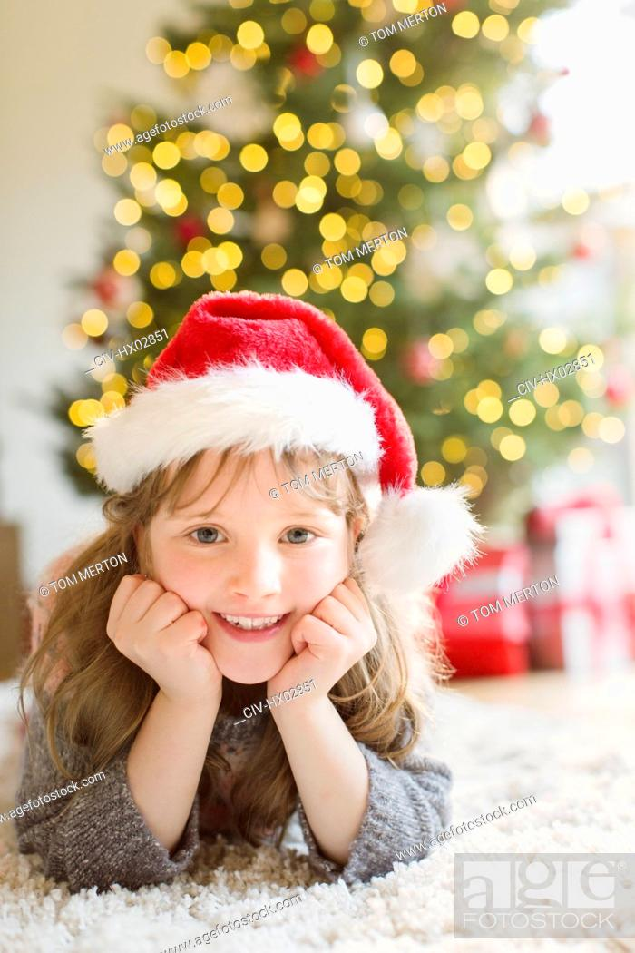 Stock Photo: Portrait smiling girl wearing Santa hat on rug in living room with Christmas tree.