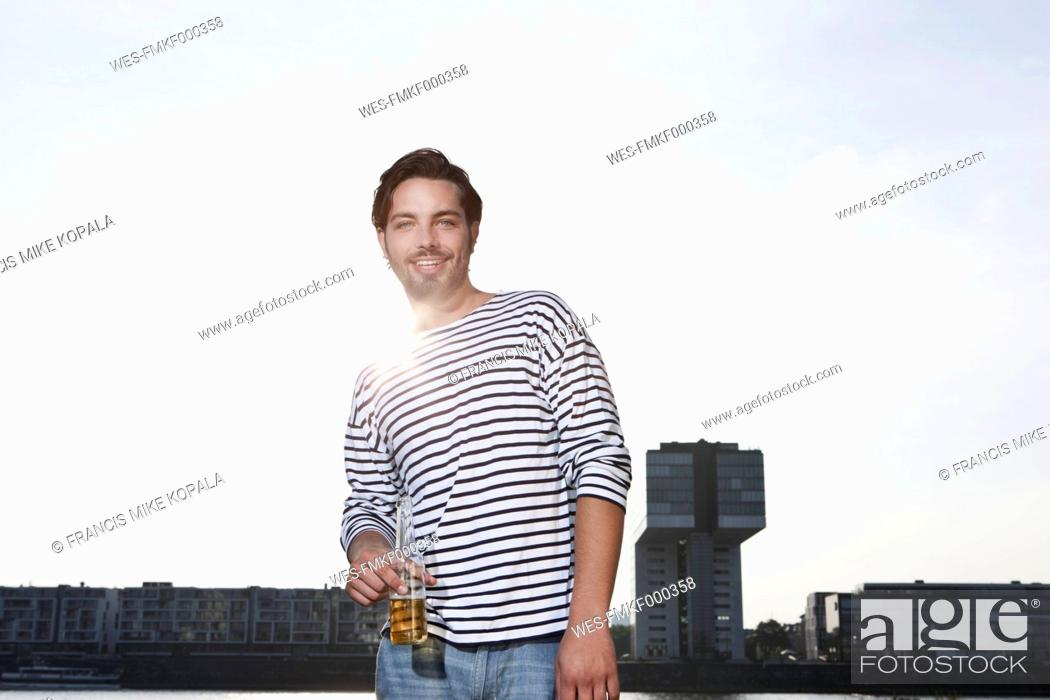 Stock Photo: Germany, Cologne, Young man with beer bottle, smiling, portrait.
