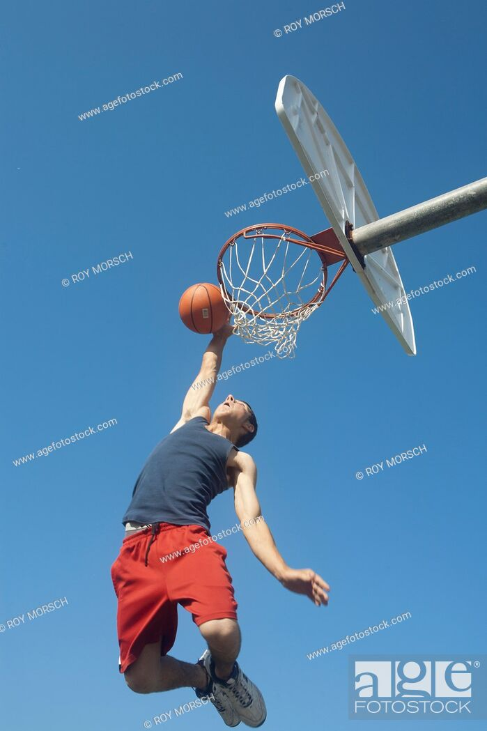 Stock Photo: Teen jumps to dunk basketball.