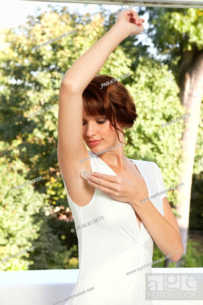 Stock Photo: Young woman applying alum stone on her armpit.