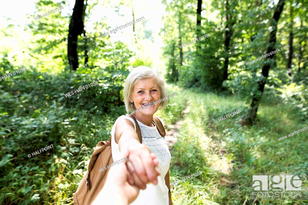 Stock Photo: Portrait of happy senior woman holding man's hand in nature.