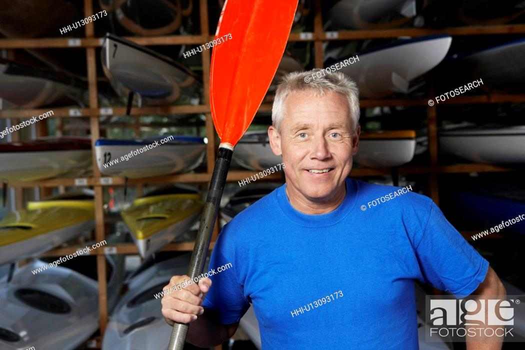 Stock Photo: Mature man holding oar by kayaks.