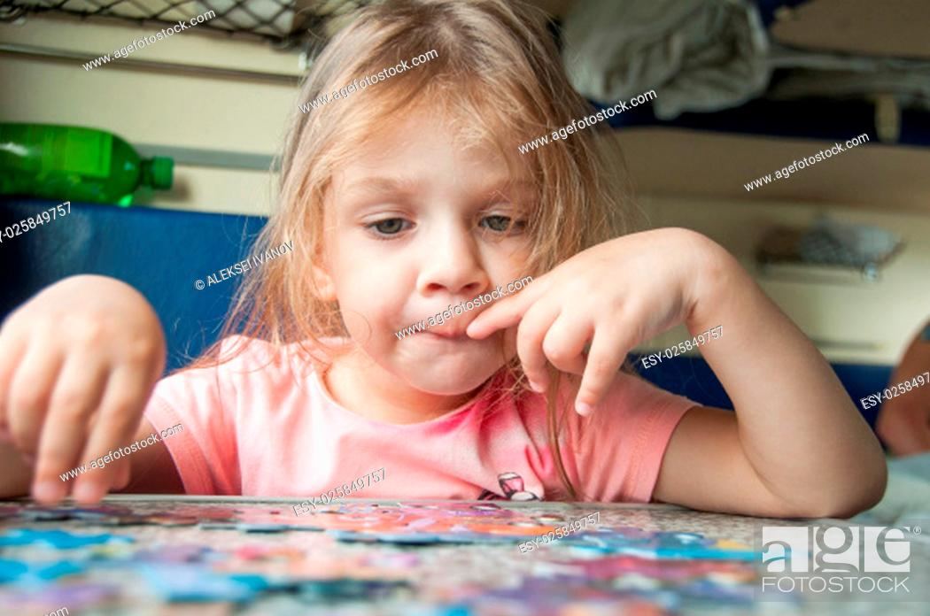 Stock Photo: The three-year girl enthusiastically collects puzzles reserved seats at a table in a train.