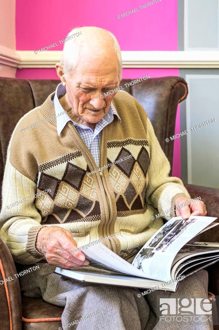 Stock Photo: Senior man sitting in a chair looking at a book about World War 2; Hartlepool, County Durham, England.