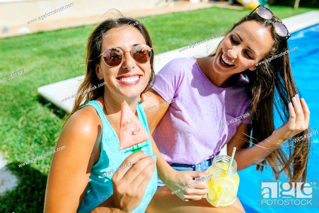 Stock Photo: Two happy young women with drink and watermelon at the poolside.