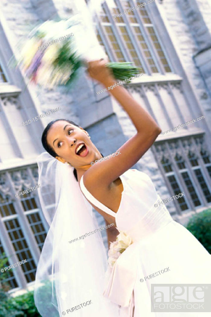 Stock Photo: Low angle view of a newlywed young woman tossing the bouquet.