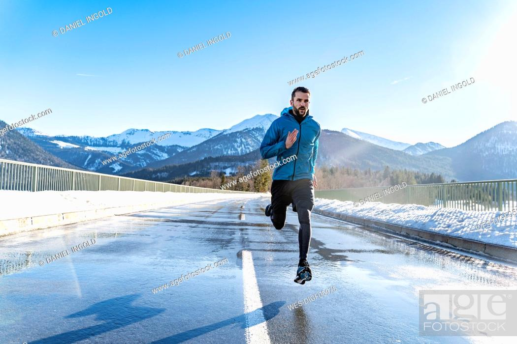 Stock Photo: Germany, Bavaria, sportive man running on a road in winter.