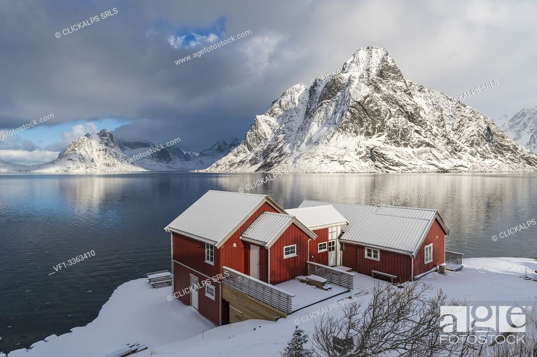 Stock Photo: Traditional 'rorbu' houses with Olstinden peak in the background in winter. Reine, Lofoten district, Nordland county, Northern Norway, Norway.