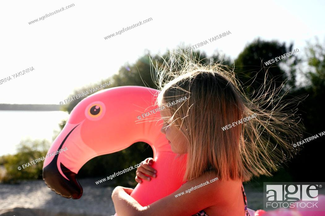 Photo de stock: Girl hugging flamingo pool float.