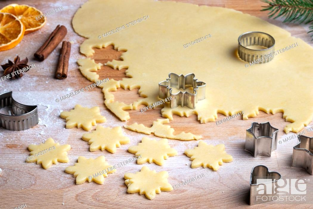 Stock Photo: Cutting out star shapes from rolled out dough to prepare traditional Linzer Christmas cookies.