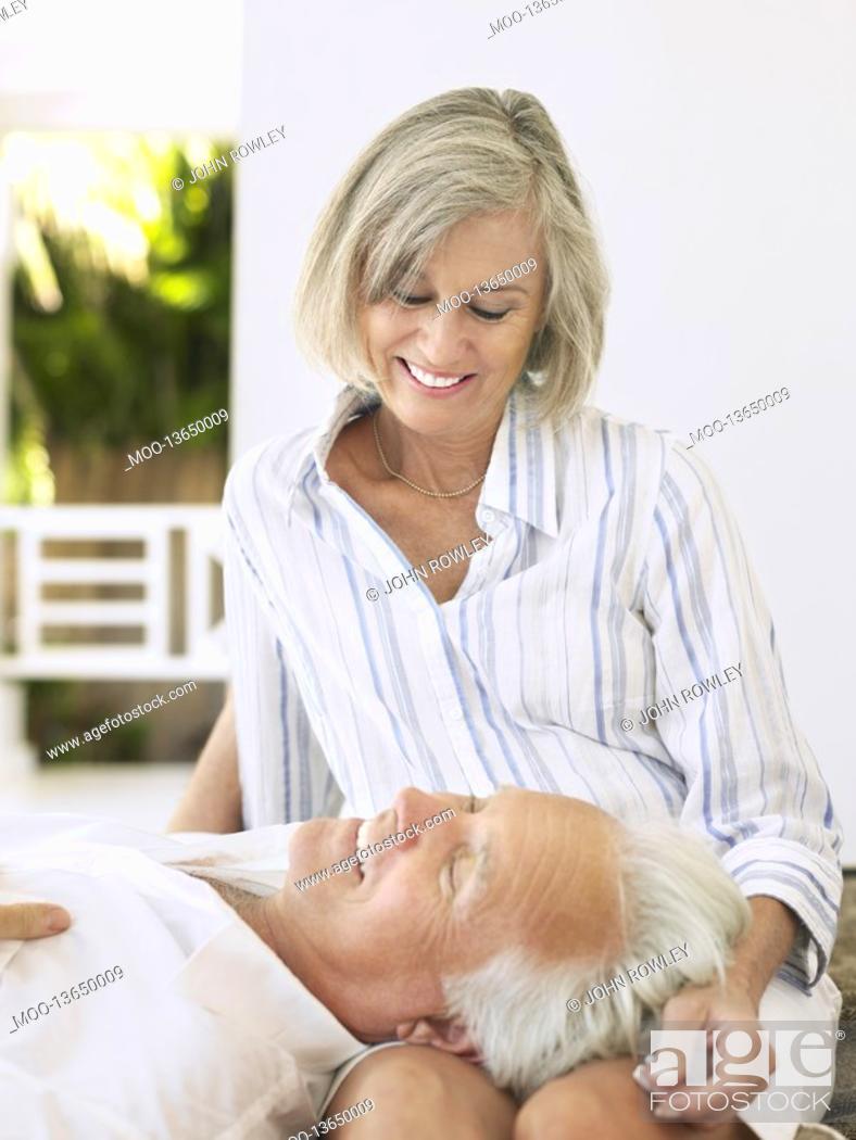 Stock Photo: Man resting head on woman's lap sitting on verandah.