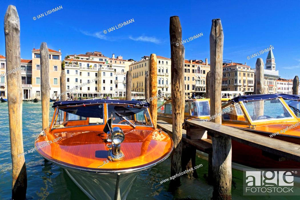 Stock Photo: Wooden water taxi boats moored on sunny Grand Canal in front of San Marco Campanile and architectural buildings in Venice, Italy.