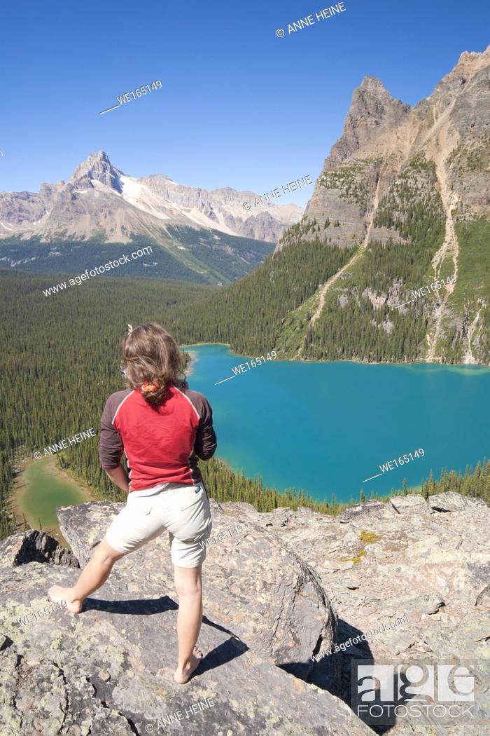 Stock Photo: female hiker enjoying view from high lookout on lake ohara. Lake O`Hara area, Yoho National Park, British Columbia, Canada.