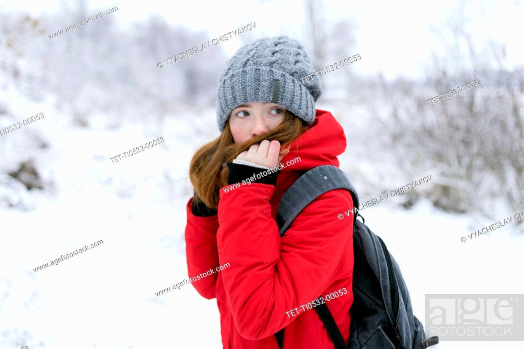 Stock Photo: Teenage girl wearing red coat and grey hat in snow.