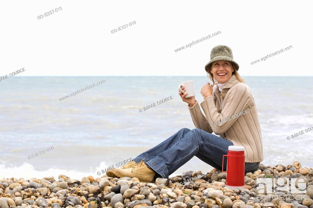 Stock Photo: Woman having a drink at the beach.