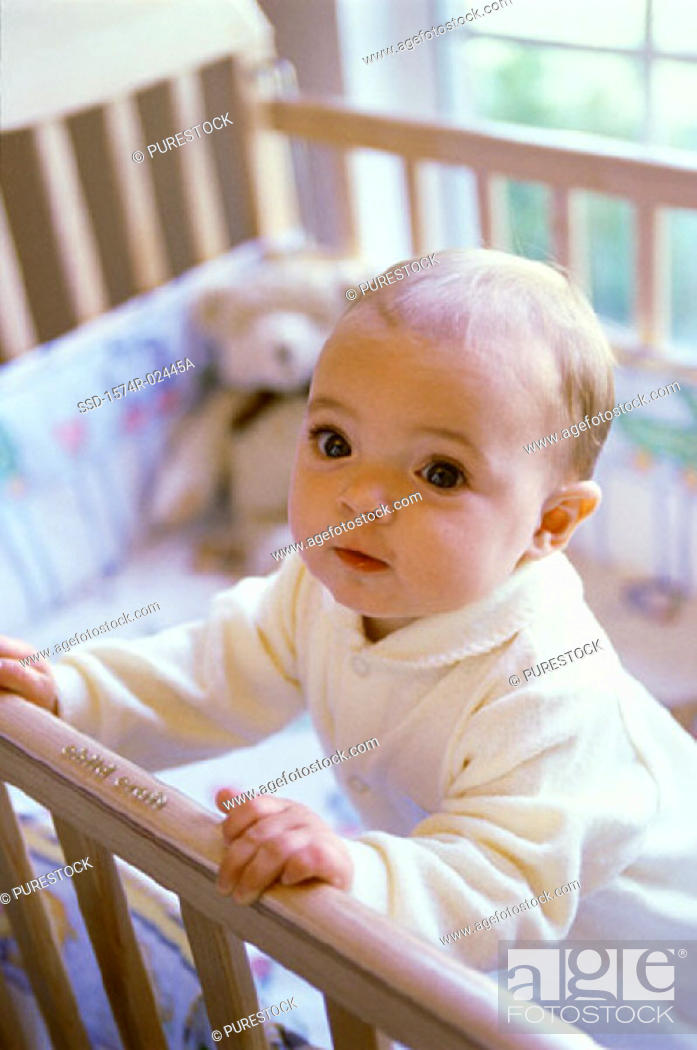 Stock Photo: Baby boy standing in a crib.