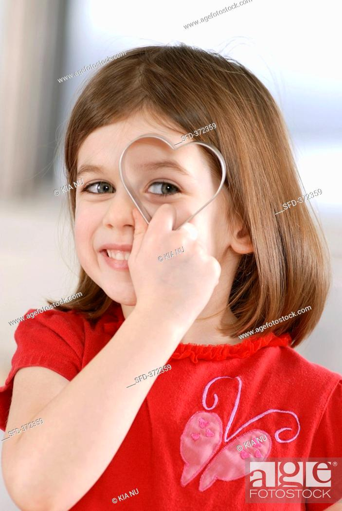 Stock Photo: Girl holding heart-shaped biscuit cutter in front of her eye.