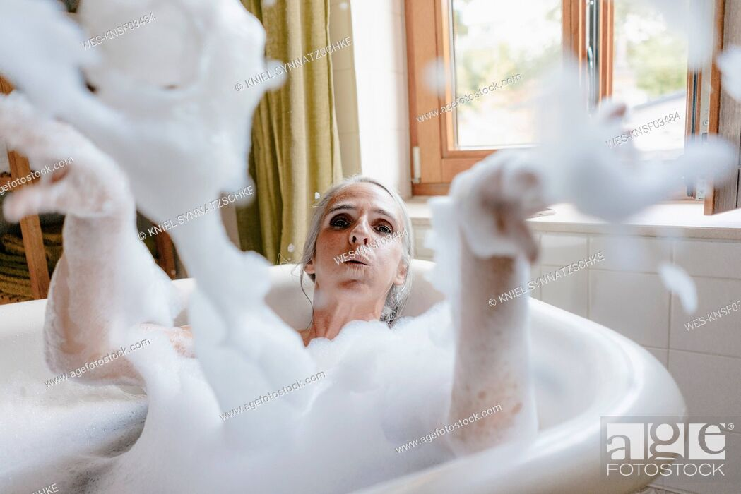 Stock Photo: Portrait of woman in bathtub playing with foam.
