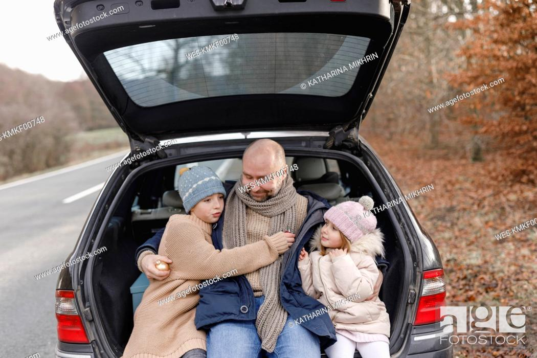 Stock Photo: Smiling father with two children sitting in car trunk at the roadside.