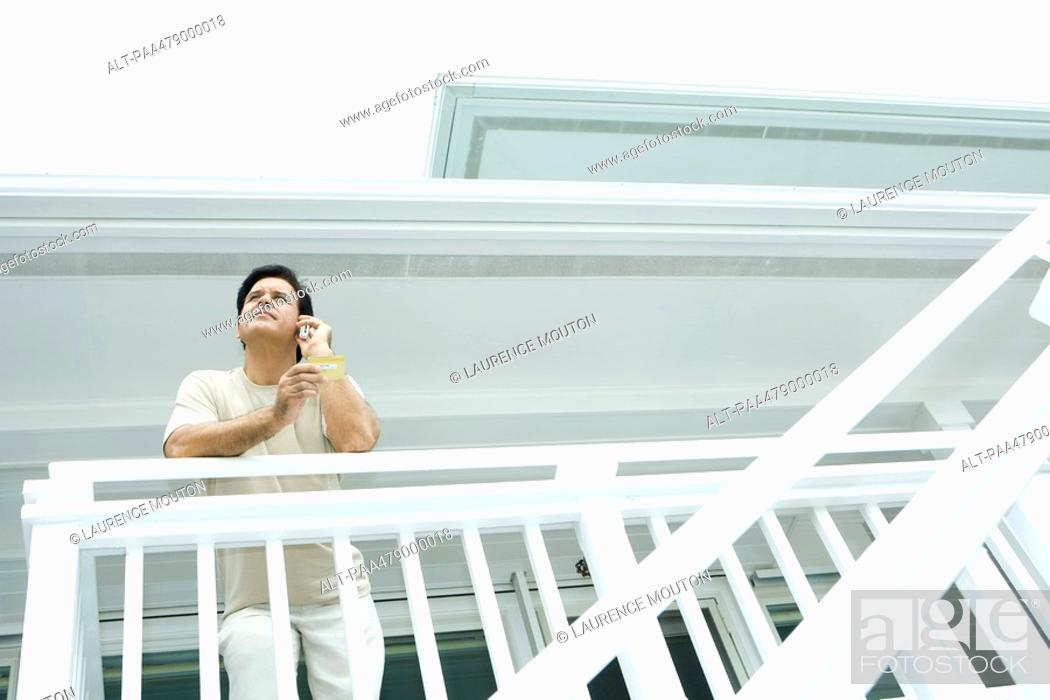 Stock Photo: Man making credit card purchase over cell phone, leaning on rail of deck, low angle view.