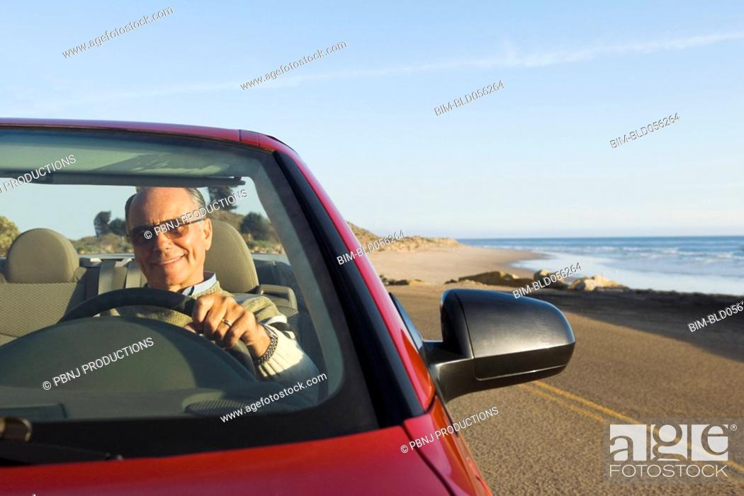 Stock Photo: Senior German man driving convertible car.