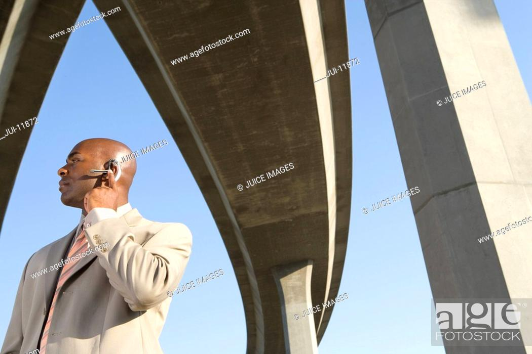Stock Photo: Businessman with hand on earpiece beneath overpasses, low angle view.