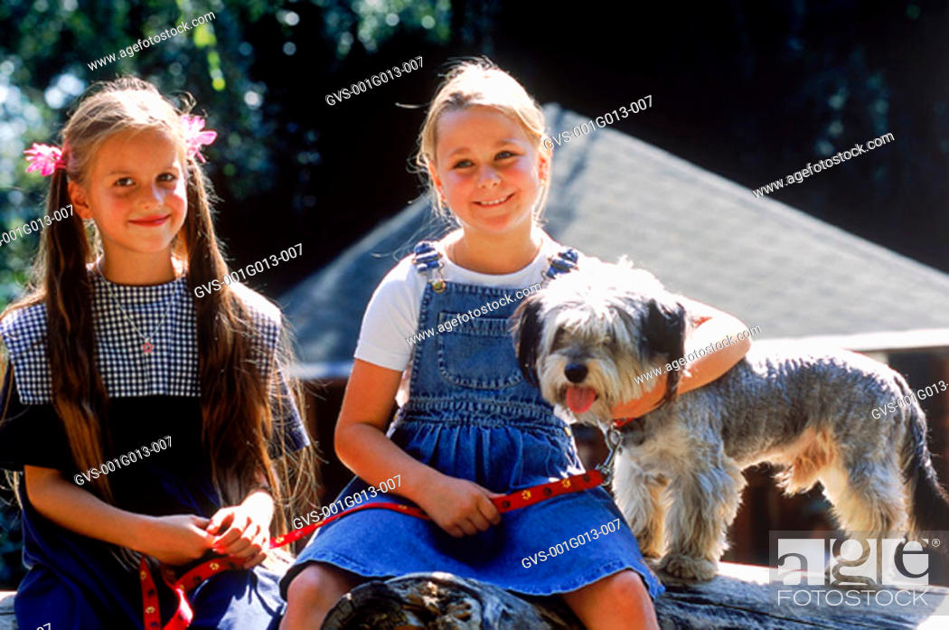 Stock Photo: Portrait of two girls with their dog.