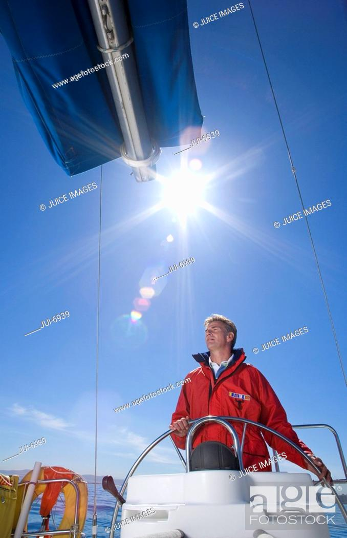 Stock Photo: Man in red jacket standing at helm of sailing boat out at sea, steering lens flare.