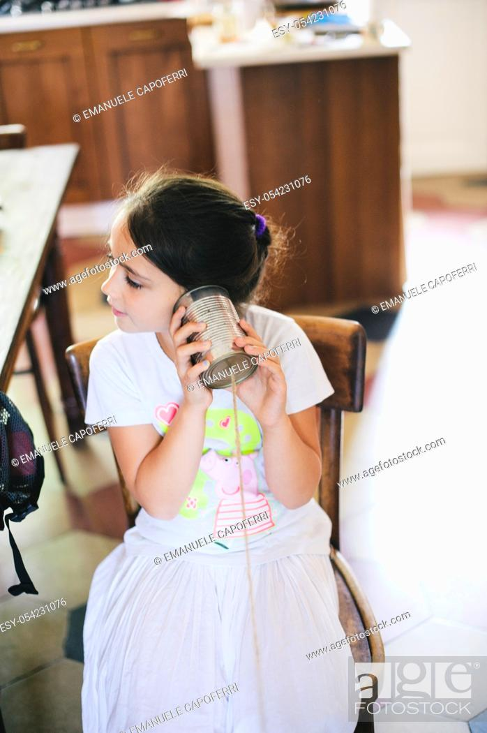 Stock Photo: Little girl in the house playing with the phone acoustic string.