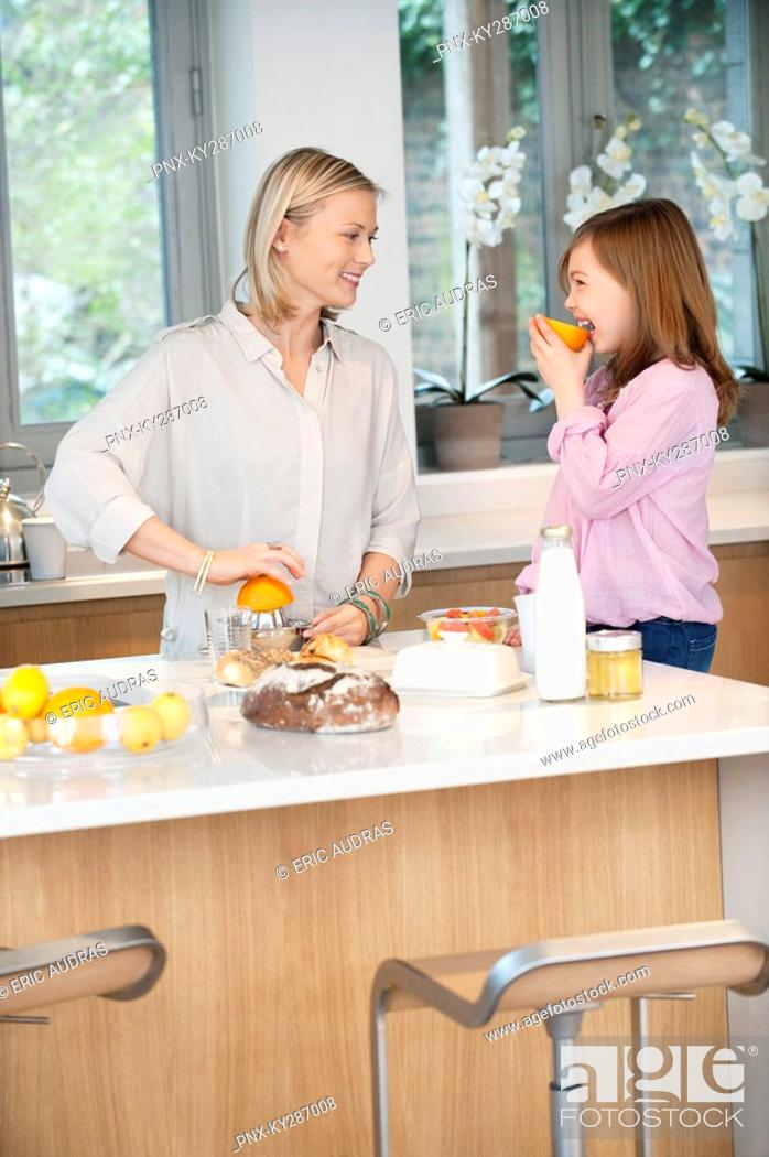Stock Photo: Woman making orange juice with her daughter in the kitchen.