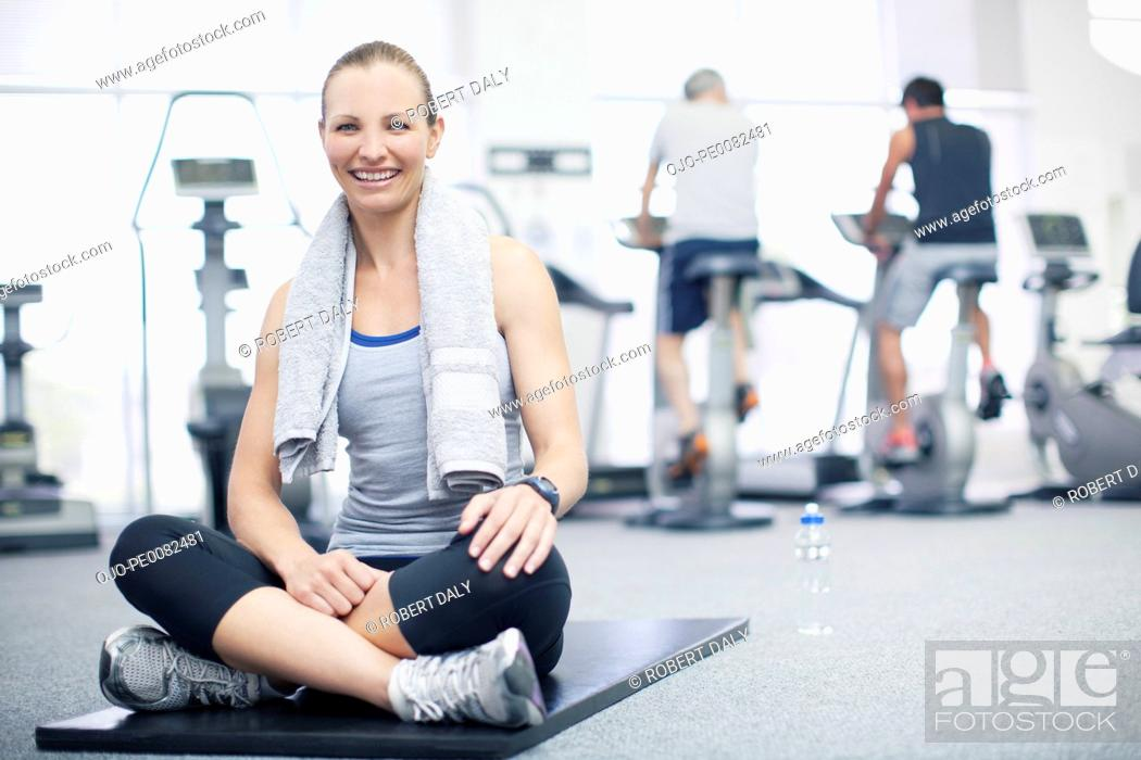 Stock Photo: Portrait of smiling woman sitting on exercise mat in gymnasium.