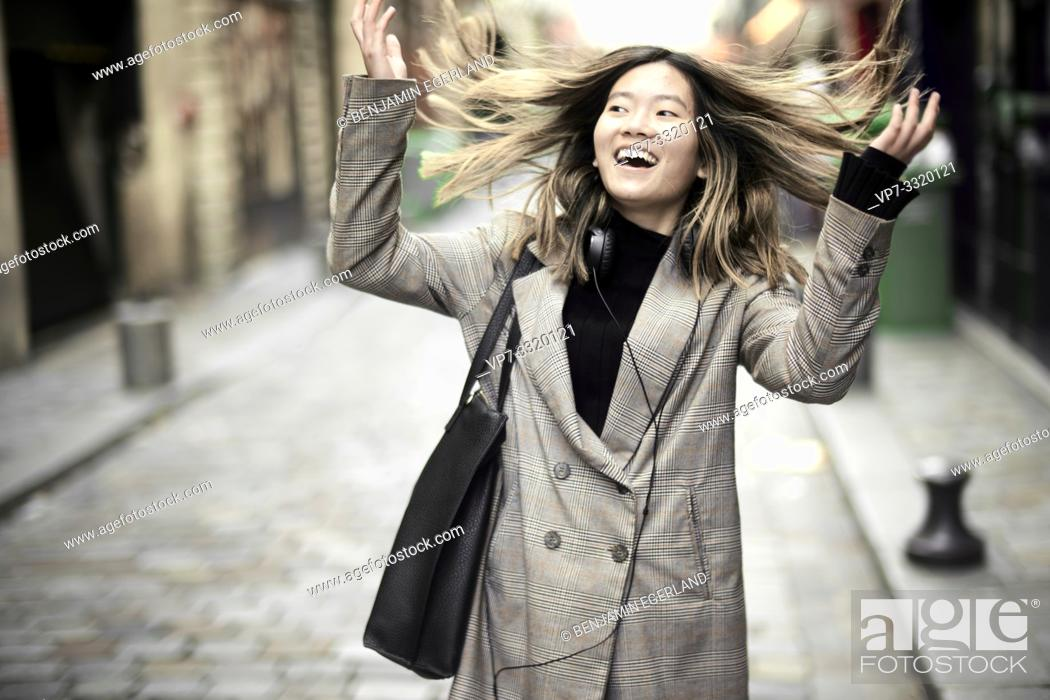 Stock Photo: young buoyant Asian woman with windswept hairs in streets of Paris, France.