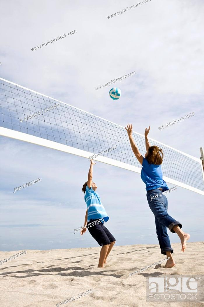 Stock Photo: Woman with her grandson playing beach volleyball.