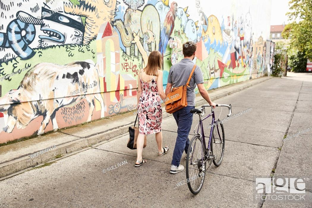 Imagen: Couple with bicycle passing wall with graffiti.