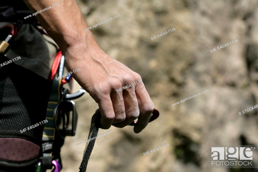 Stock Photo: Male hand with a carabiner on a rope in front of a rocky wall, close-up, selective focus.