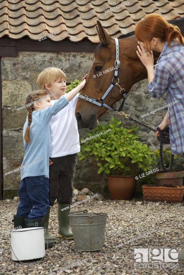 Stock Photo: Mother and children 5-6 7-9 stroking horse outside stable.