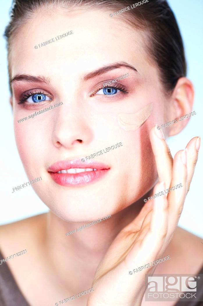 Stock Photo: Young woman applying foundation.