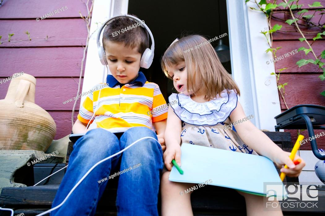 Stock Photo: Brothers listening to music with headphones on the outside.