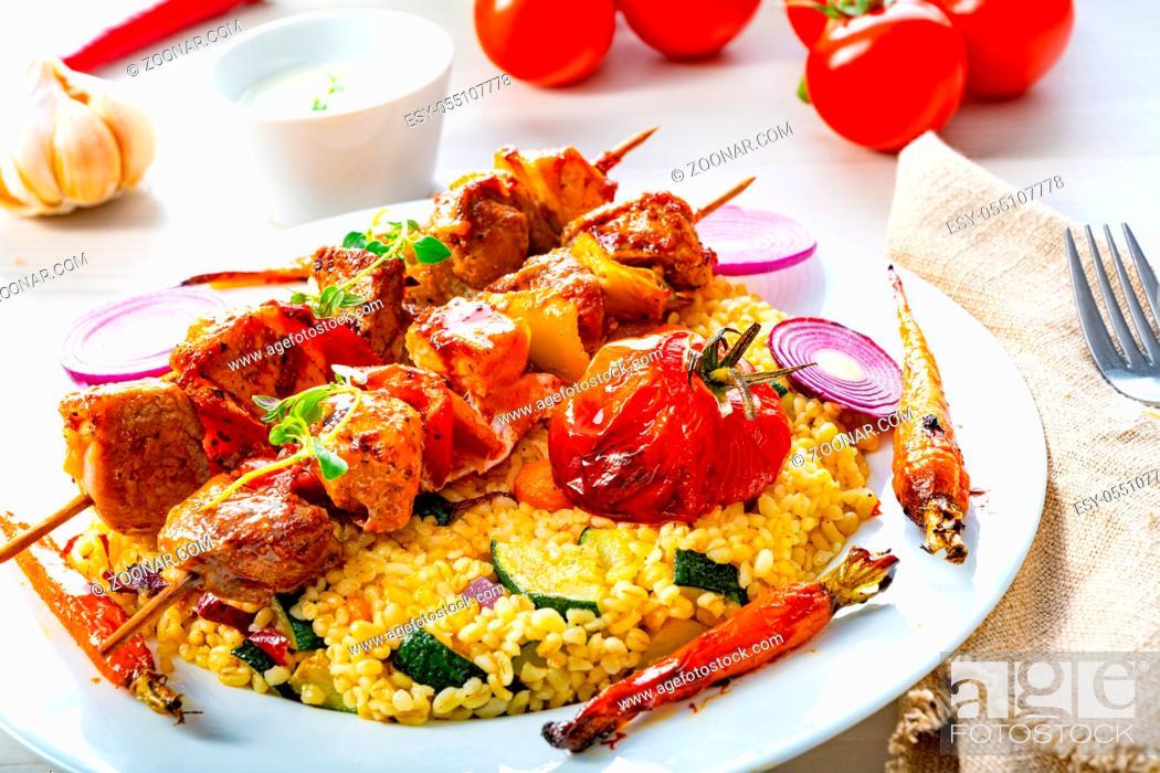 Stock Photo: Shish kebabs with vegetables and bulgur.