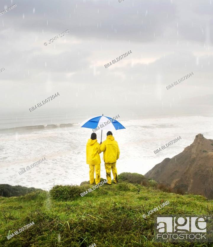 Stock Photo: Hispanic couple under umbrella on cliff.
