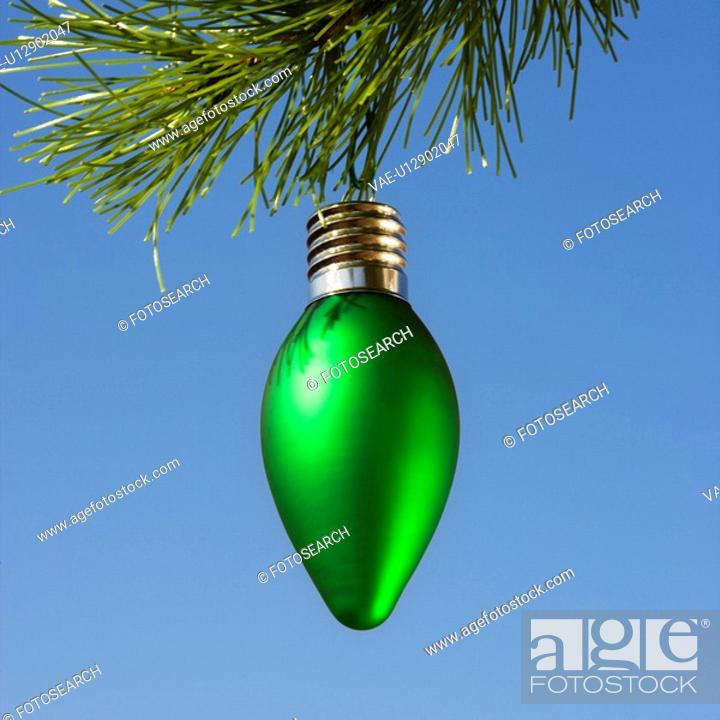 Stock Photo: Green ornament hanging on Christmas tree branch against blue background.