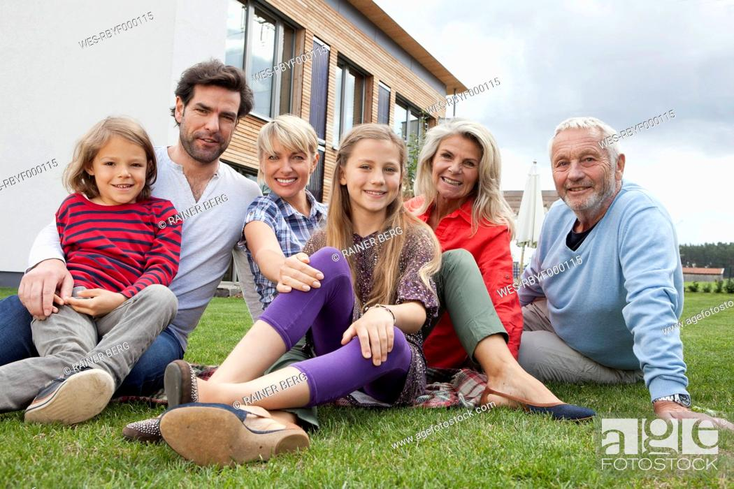 Stock Photo: Germany, Bavaria, Nuremberg, Family sitting in front of house, smiling, portrait.